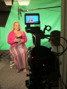 Blond woman in from of a green screen with a camera in front of her