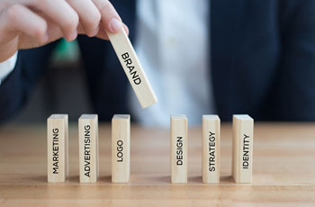 Business person with row of domino with keywords; marketing, advertising, logo, brand, design, strategy and identity