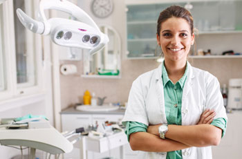 Female dentist in operatory, smiling with arms crossed